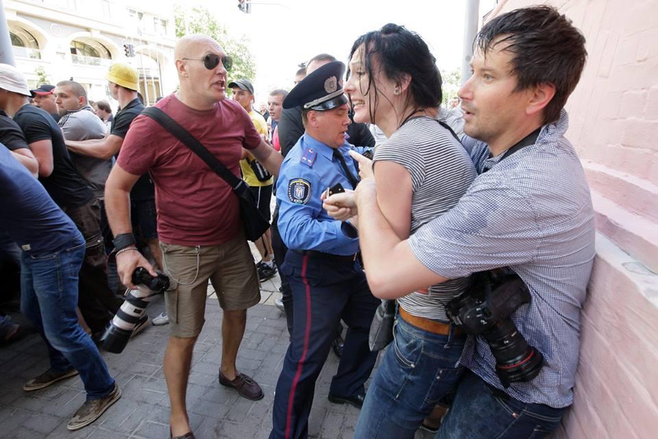 На фото: подполковник милиции обернулся спиной к возможным нападающим, Содель держит избитую Сницарчук