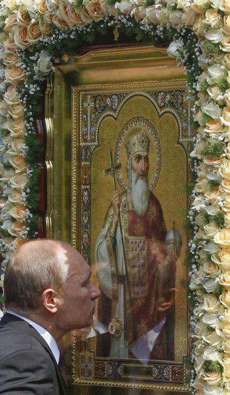 Президент РФ Владимир Путин целует икону во время молебна