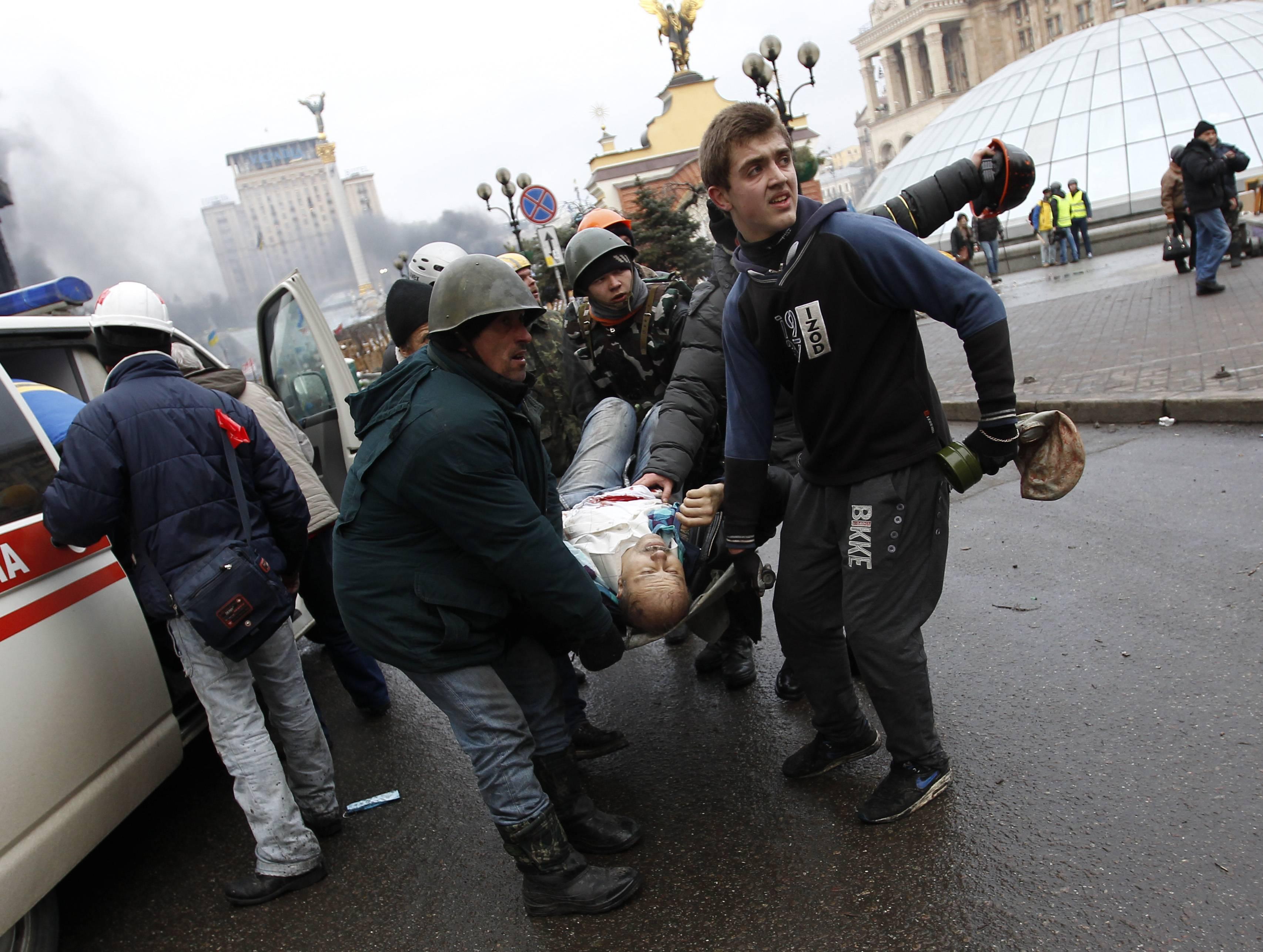 Несут раненого на Майдане
