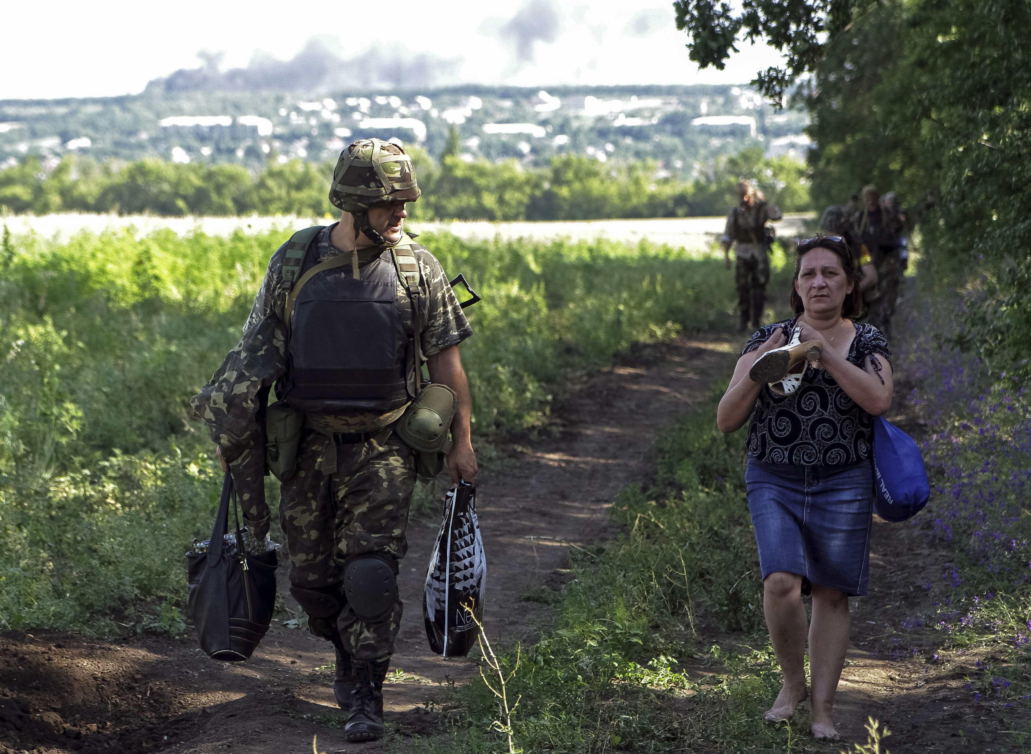 Украинский военный помогает беженцам уйти из зоны конфликта