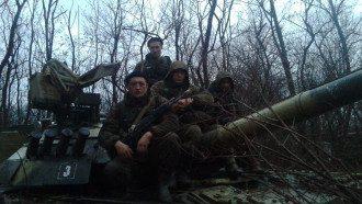 Полевой лагерь россиян в лесу, где замаскирована боевая техника, включая танк Т-80.