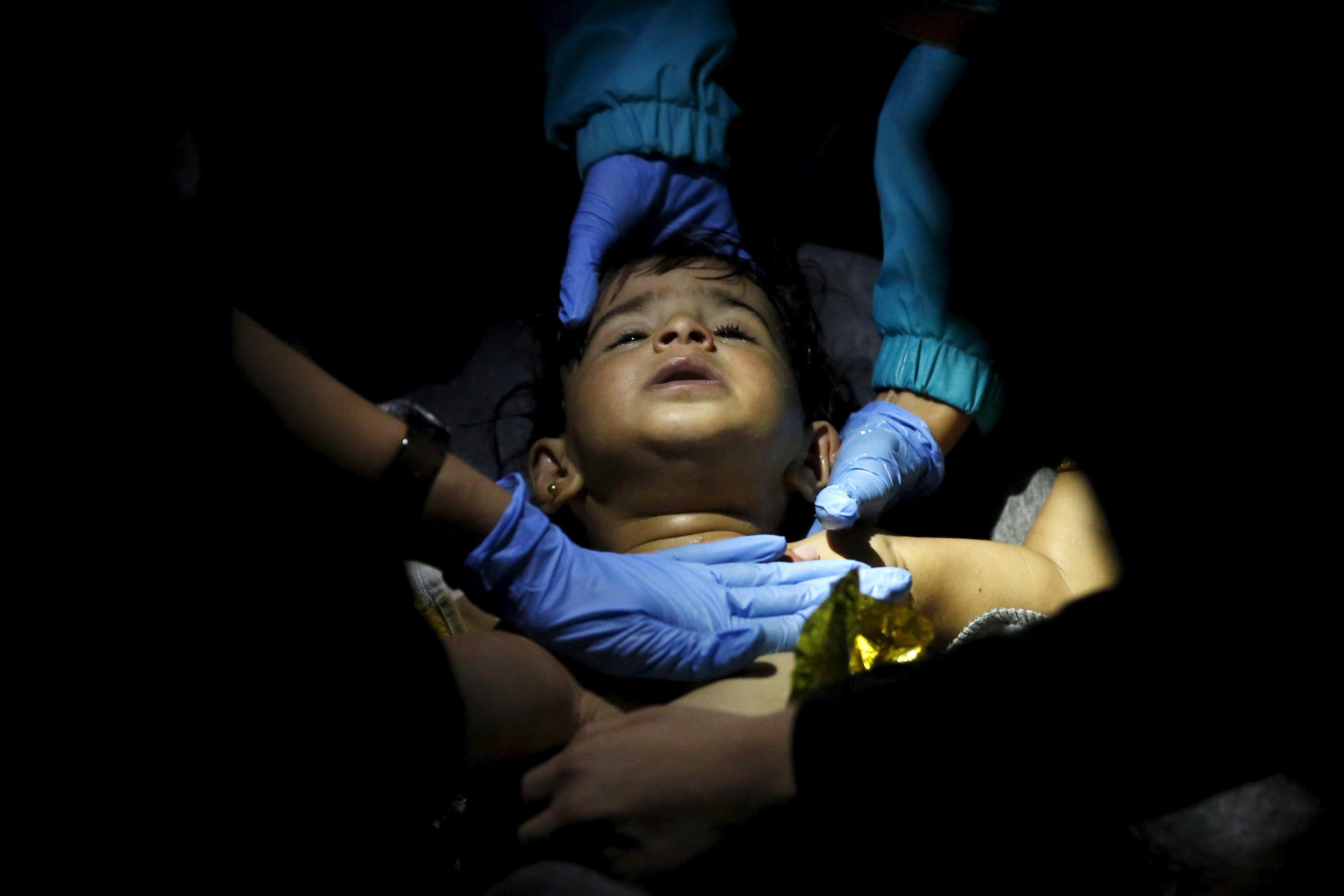 Медики и спасатели откачивают спасенного малыша