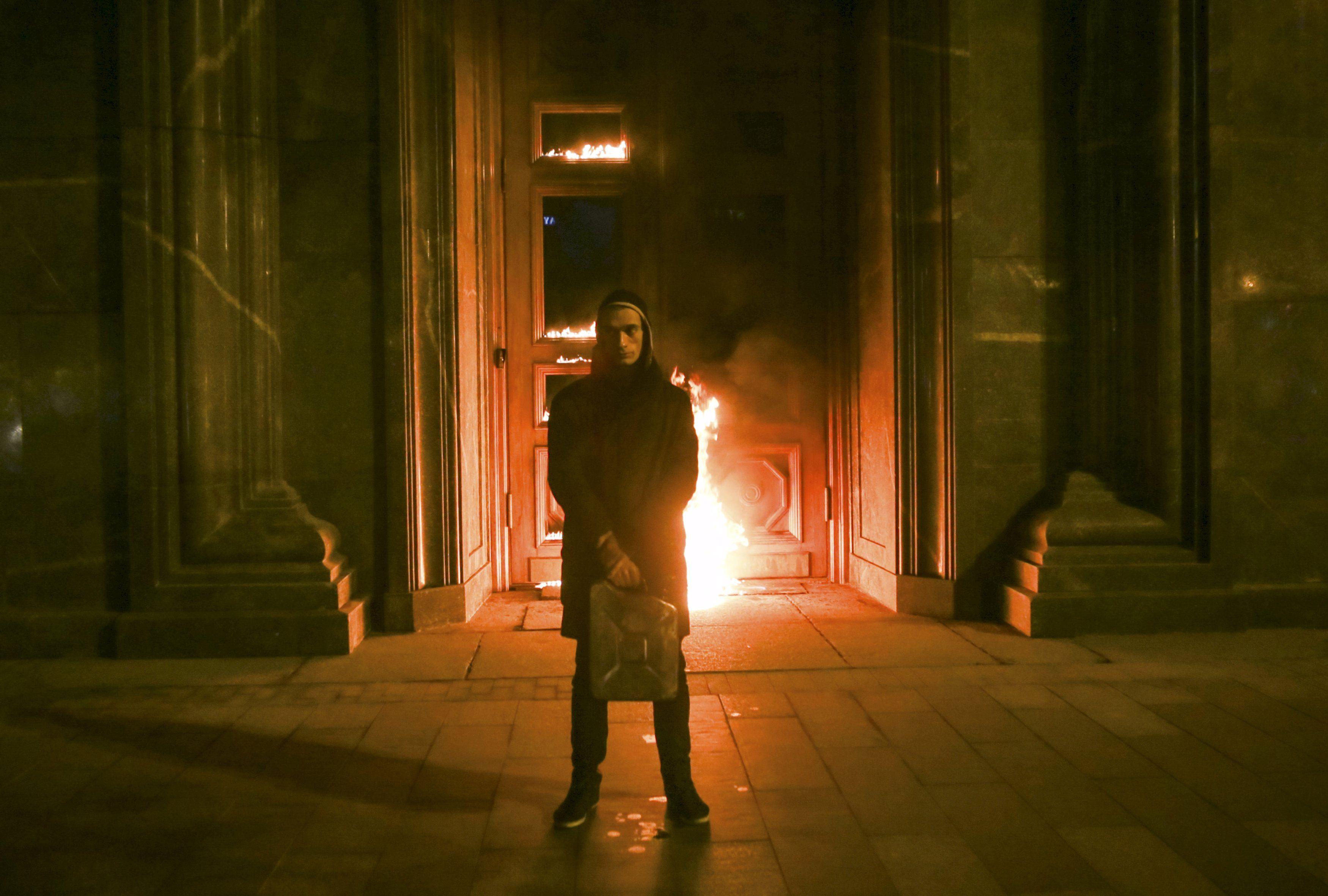 Петр Павленский на фоне горящей двери ФСБ