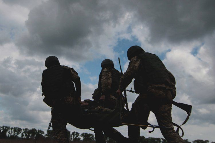 Украинские военные выносят раненого товарища