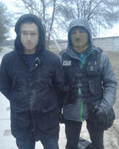 Задержанный злоумышленник и сотрудник СБУ