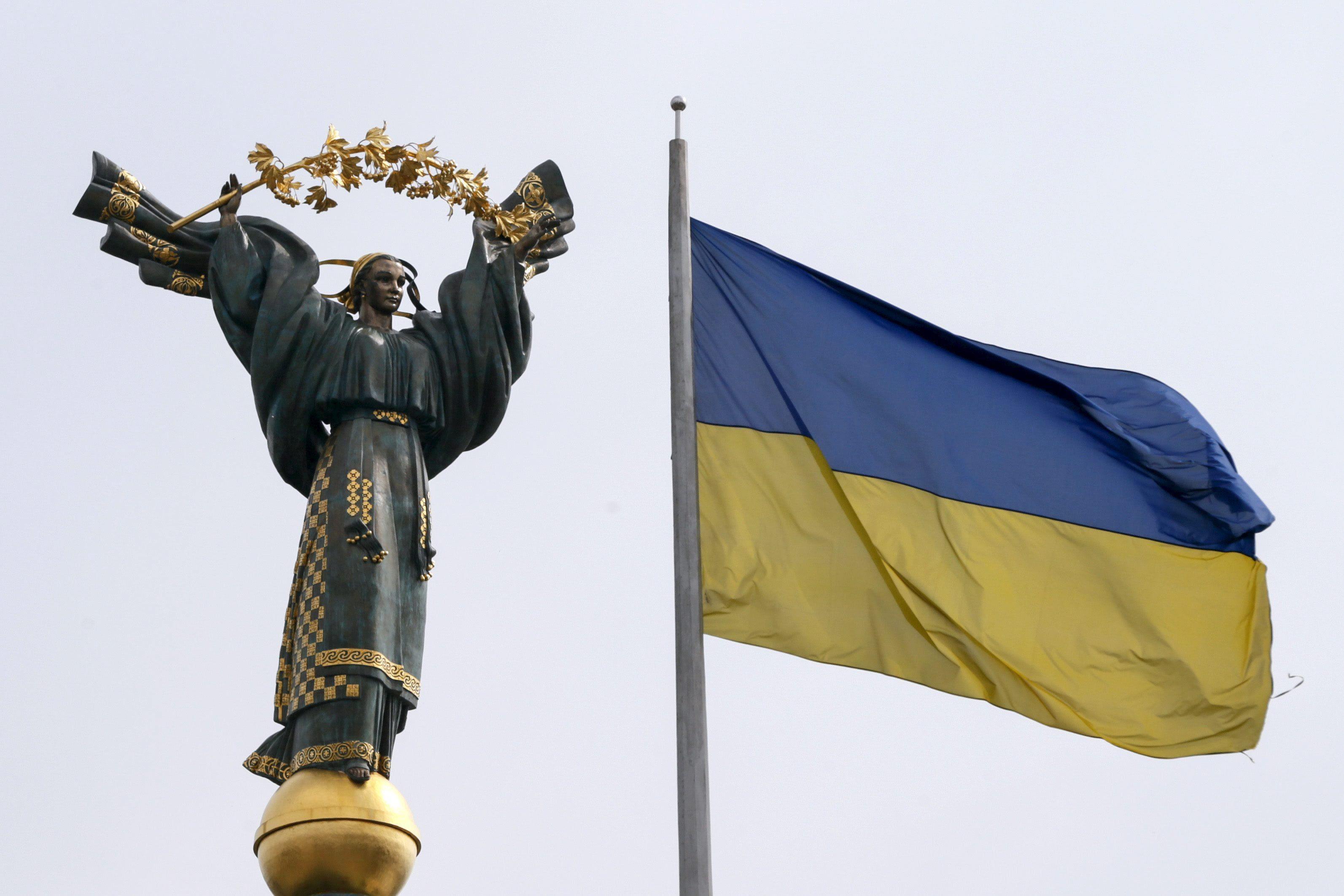 Монумент Независимости Украины, расположенный на Майдане в Киеве, и флаг страны, иллюстрация