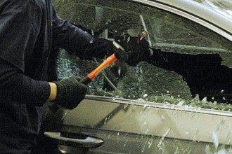 Злоумышленник выбивает окно машины, иллюстрация
