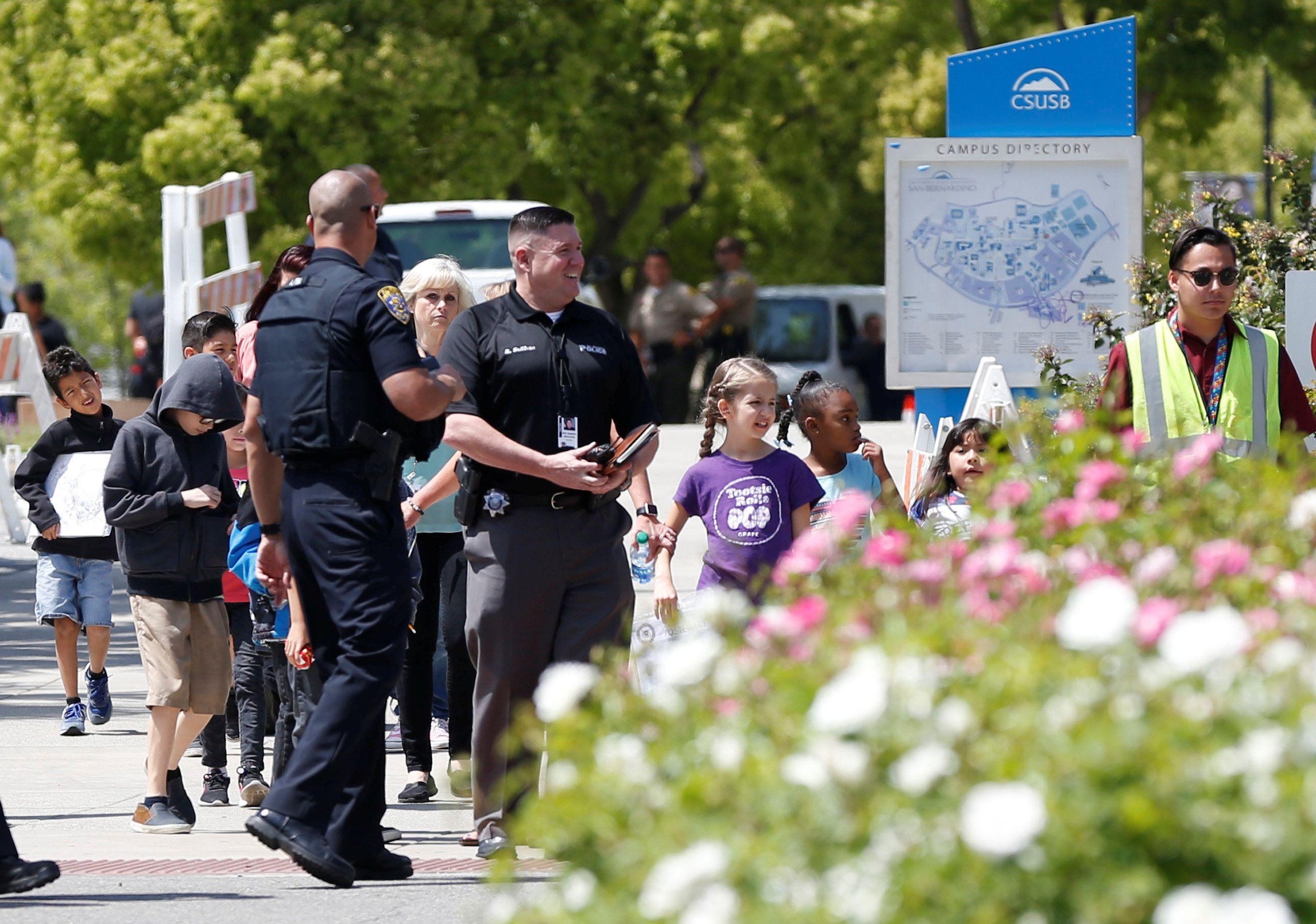 Сотрудники полиции эвкуируют детей.
