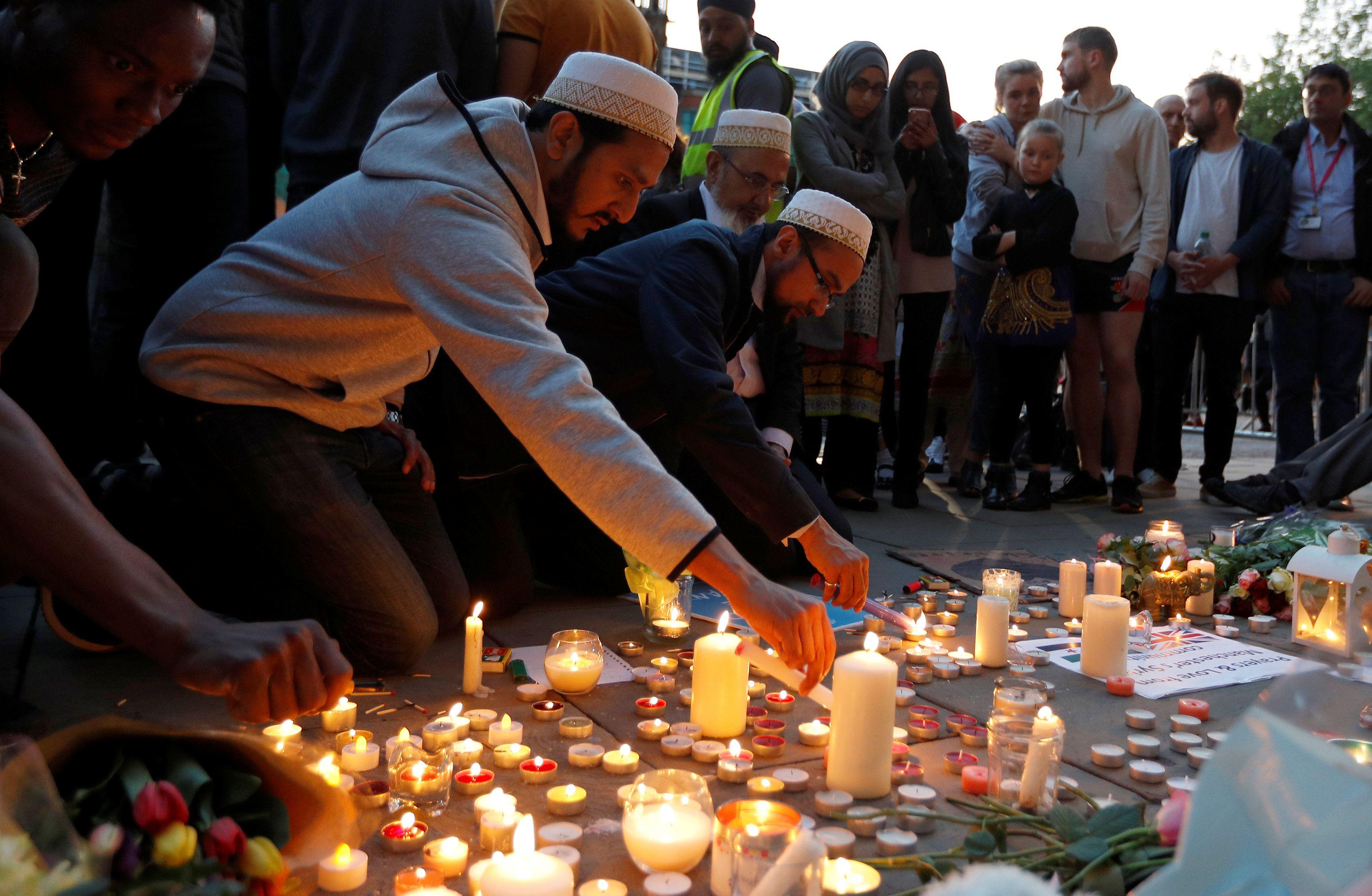 Люди зажигают свечи после теракта в Манчестере.