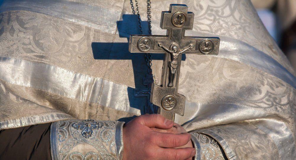 Православный крест в руках священника