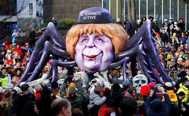 Канцлер Германии Ангела Меркель в образе паучихи на костях уничтоженных противников
