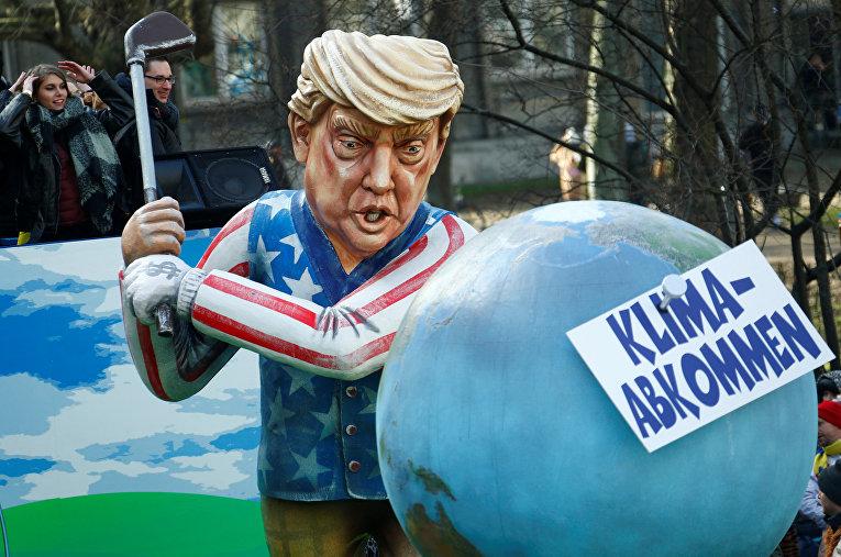Президент США Дональд Трамп, который замахивается клюшкой для гольфа на договор по климату
