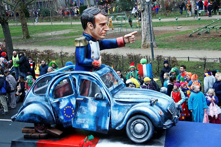 Президент Франции Эмануэль Макрон в манере Наполеона указывает дорогу на полуразвалившемся авто с символикой ЕС