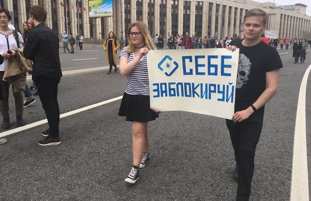 Молодые люди несут плакаты с пожеланиями главе Роскомнадзора.